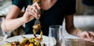 En kvinna njuter av mat med rött vin